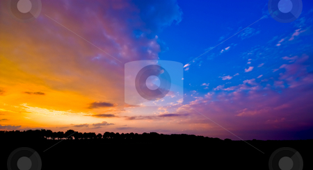 Blue sunset stock photo, Sunset with a piece of blue sky and silhouette of a landscape by Karin Claus