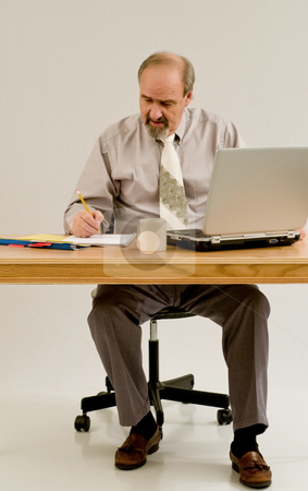 Businessman taking notes from a computer search stock photo, Businessman seated at a desk with a laptop computer by RCarner Photography