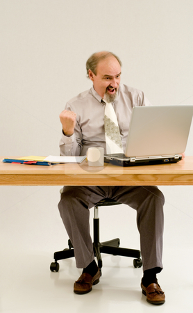 Businessman likes what he sees on laptop. stock photo, Businessman seated at a desk with laptop and files. by RCarner Photography