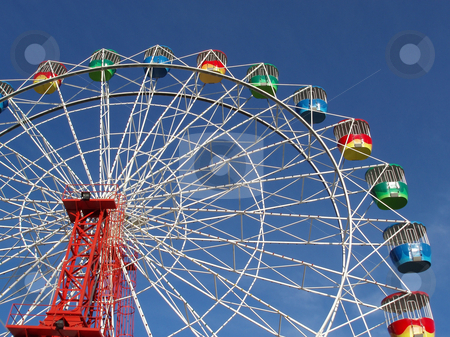 Ferris wheel stock photo, A colourful fairground wheel against a blue sky by Stephen Gibson
