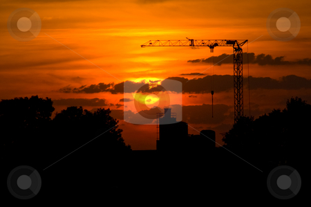 Crane sunset stock photo, crane with a  sunset and silhouette of a factory in the back by Karin Claus