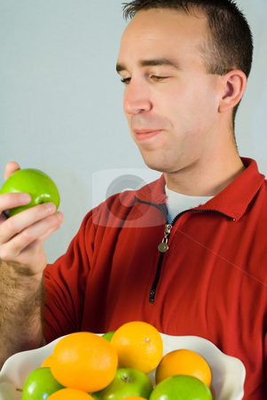 Healthy Snack stock photo, A young man holding an apple and a platter of fruit by Richard Nelson