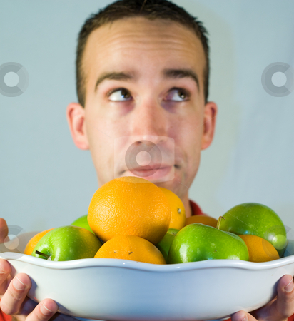 Healthy Snack stock photo, A young man holding a bowl of healthy apples and oranges by Richard Nelson