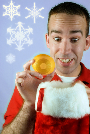 Christmas Oranges stock photo, A young man looking happy at finding an orange in his Christmas stocking by Richard Nelson