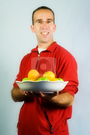 Healthy Eating stock photo, A young man wearing red, holding a platter of apples and oranges by Richard Nelson