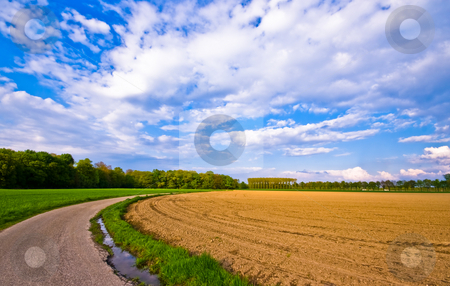 Rural scenery stock photo, Country road through a rural farmlandscape with nice cloudscape by Karin Claus
