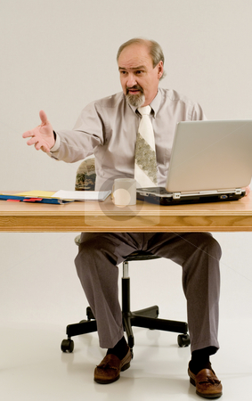 Businessman gestures as he offers solution stock photo, Businessman seated at a table with files and a laptop by RCarner Photography
