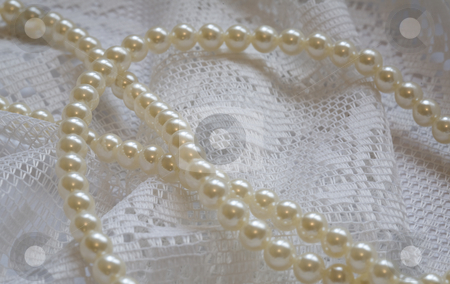 Pearls and lace stock photo, A necklace of pearls lying on a lace background by Norma Cornes