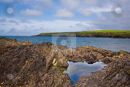Rock pool stock photo, A rock pool with the sea and cliffs behind by Norma Cornes