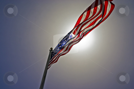 Dramatic US Flag stock photo, The US flag dramatically backlit by the sun. by Marc Saegesser