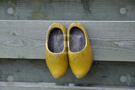 Clogs stock photo, Dutch wooden shoes hanging from a rustic wooden fence by Gert-Jan Kappert