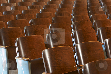 Chairs alone stock photo, Rows of wood chairs in an old auditorium by Glen Jones