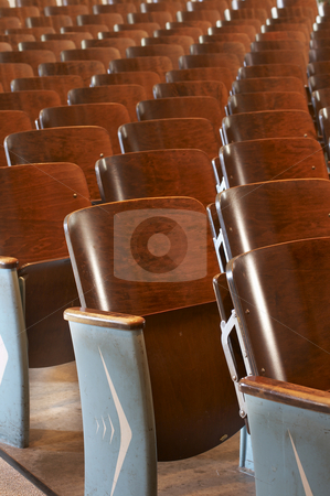 Chairs in a row stock photo, Rows of wood chairs in an old auditorium by Glen Jones