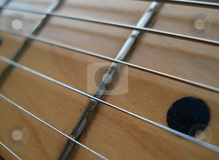Electric Guitar Neck stock photo, The neck of an electric guitar stretched out across the shot. by Ben O'Neal