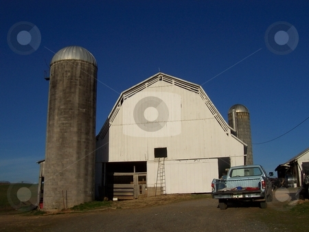 Barn and Concrete Silos stock photo, White barn and two concrete silos used for storage at a dairy farm in Tennessee by Krystal McCammon