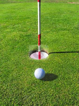 A golf ball lands near the hole on the green. stock photo, A golf ball lands near the hole on the green. by Stephen Rees