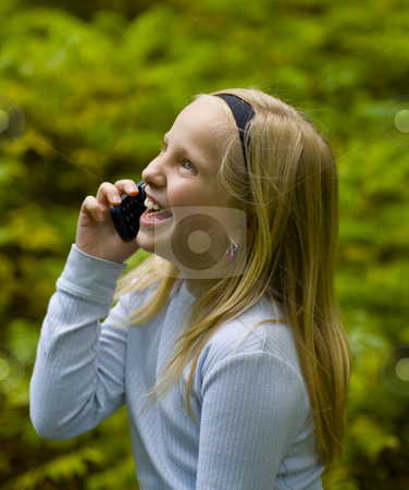 Happy Girl on Phone stock photo, A happy girl on a cell phone outdoors by John McLaird