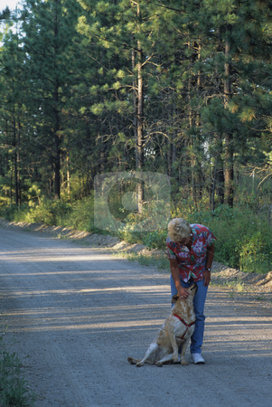 Woman And Her Dog stock photo, Woman Walking Her Dog Down A Rural Road by Mallorey Orcutt