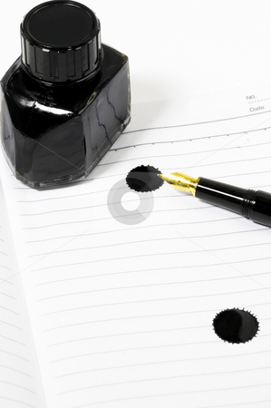 Fountain pen and notebook stock photo, Classic black fountain pen on open notebook with ink bottle with stain on page by Francesco Perre