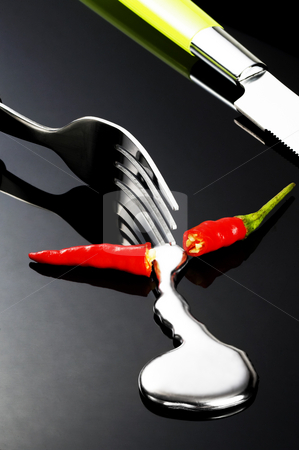 Red chili pepper stock photo, Red chili pepper melting a fork while be cutted on a black stone by Francesco Perre