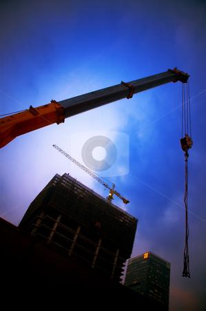 Construction cranes stock photo, Construction cranes on night ove a blue sky by Francesco Perre