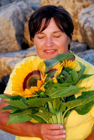 Mature woman flowers stock photo, Mature woman with bouquet of sunflowers by Elena Elisseeva