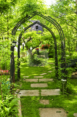 Lush green garden stock photo, Lush green garden with wrought iron arbor by Elena Elisseeva