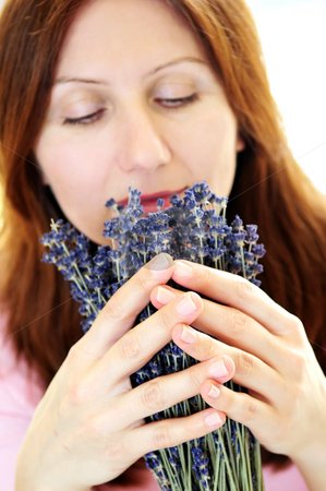 Woman smelling lavender stock photo, Mature woman smelling lavender flowers focus on hands by Elena Elisseeva