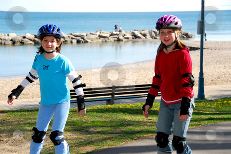 Girls rollerblade stock photo, Two girls rollerblading on lake shore trail by Elena Elisseeva