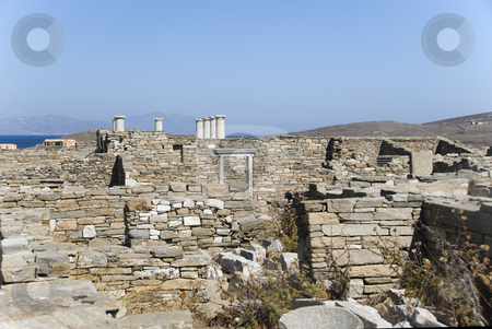 Ancient Ruins on Delos stock photo, Delos is an Aegean island, now uninhabited but with extensive archeological sites. It was a very rich successful trading center and place of pilgrimage, with a huge slave market, that was invaded, looted and destroyed in early AD and was abandoned for almost 2000 years. Now tourists visit in large numbers on day trips by Angela Arenal