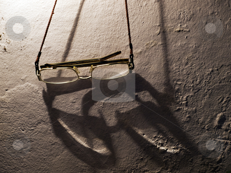 Eye glasses stock photo, Old glasses hung on the wall with the ambient lighting in the background. by Sinisa Botas