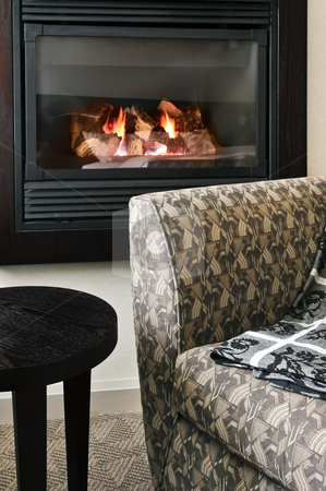 Fireplace and armchair stock photo, Fireplace and cozy armchair in living room by Elena Elisseeva