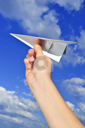 Hand holding paper airplane stock photo, Child's hand holding a paper airplane on blue sky background by Elena Elisseeva