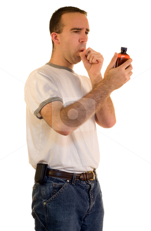 Coughing Man stock photo, A young man coughing from a cold, and holding medicine by Richard Nelson
