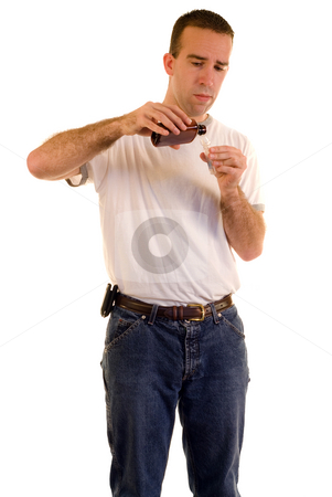 Measuring Cough Medicine stock photo, A man measuring some cough medicine, isolated against a white background by Richard Nelson