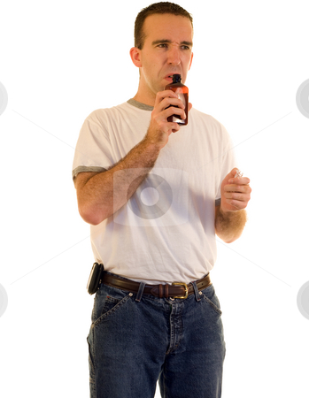Man Smelling Cough Medicine stock photo, A you man smelling some cough medicine, isolated against a white background by Richard Nelson