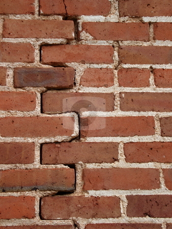 Vertical Red Brick Wall stock photo, A red brick wall has a long crack from top to bottom. by Ben O'Neal