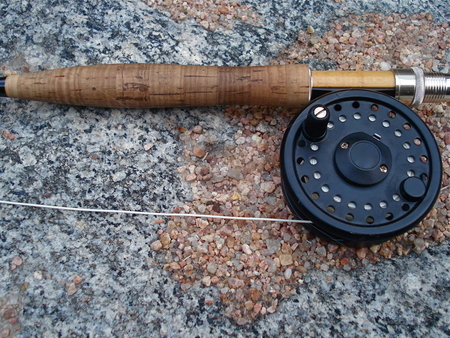 Fly Rod on a Rock stock photo, A fly rod laying on a rock near a Colorado Stream. by Ben O'Neal