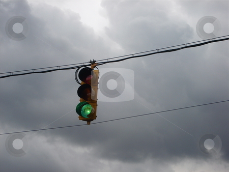 Horizontal Cloudy Sky Traffic Signal stock photo, A traffic signal indicates the go light on a stormy evening in Colorado. by Ben O'Neal