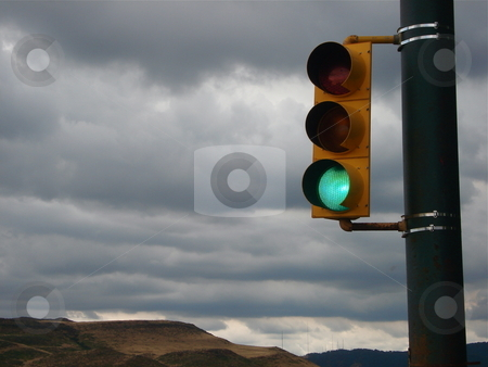 Traffic Signal in front of Colorado Mountains stock photo, A traffic signal stands in front of some Colorado mountains on a stormy evening. by Ben O'Neal