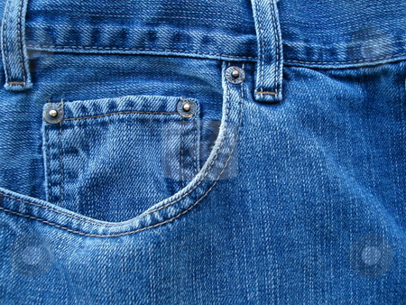 Blue Jean Pockets stock photo, A pair of blue jeans reveals details in the evening sunlight from a nearby window. by Ben O'Neal