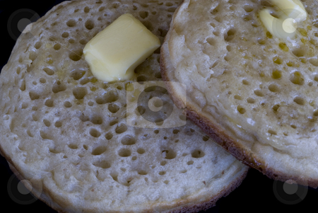 Buttered crumpets stock photo, Two hot crumpets with melted butter, isolated on a black backdrop by Stephen Gibson