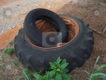 Two old, used tractor tires stock photo, One large tractor tire holding a smaller tire. Both done with their work on the farm. by Krystal McCammon