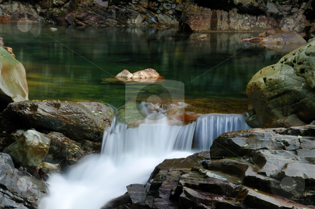 Wild stream flowing through rocks stock photo, Wild stream flowing through rocky river bed by Nilanjan Bhattacharya