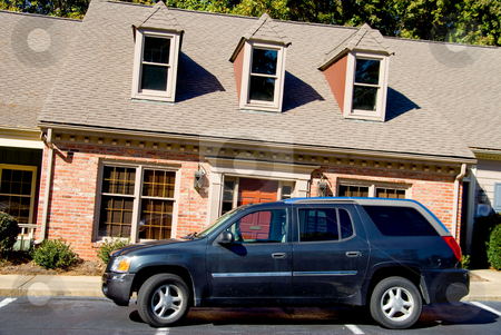 Leaning Apartments stock photo, An SUV parked in fron of a leaning apartment building. by Robert Byron