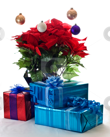 The Christmas spirit of giving stock photo, Presents and Poinsettia under floating ornaments. by RCarner Photography