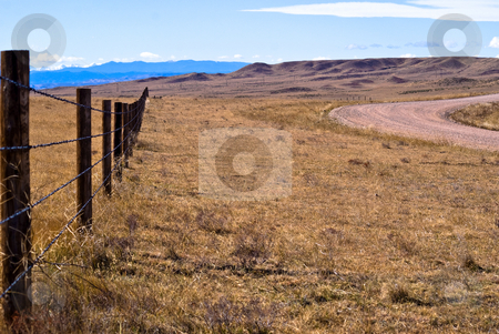 High plains fence stock photo, A barbed wire fence runs along a gravel road, east of the Rocky Mountains by RCarner Photography