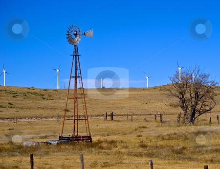 The old technology and the new stock photo, An old wind driven water well is surrounded by new wind generators. by RCarner Photography