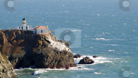 Lighthouse stock photo, Lighthouse on a rocky coast overlooking the ocean by Denis Radovanovic