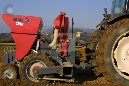 Tractor planting in soil stock photo,  by Michael Schweres